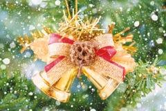 Campanas de la cinta de la Navidad que cuelgan en fondo borroso del árbol con efecto de la nieve Fotos de archivo