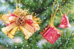 Campanas de la cinta de la Navidad y ejecución de la decoración del ornamento en árbol con efecto de la nieve Fotos de archivo