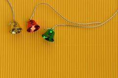 campanas de la Navidad coloridas en fondo amarillo Imagenes de archivo