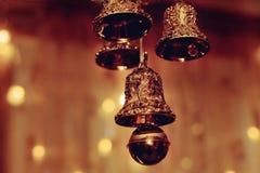 Campanas de oro del Año Nuevo de la Navidad en una ventana en un fondo oscuro imagen de archivo