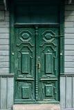 Campanas de puerta talladas de madera viejas pintadas con la pintura de aceite verde con la manija de bronce y la cerradura de ac foto de archivo libre de regalías