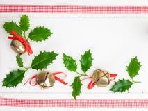 Campanas de trineo y hojas del acebo Fotografía de archivo libre de regalías