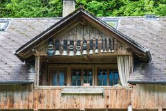 Campanas decorativas de la vaca debajo del tejado de una choza alpina de la montaña fotos de archivo