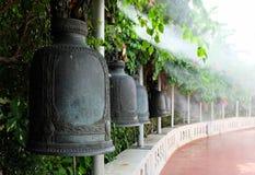 Campane buddisti fatte di ferro/di bronzo che appende in una fila curva Fotografia Stock