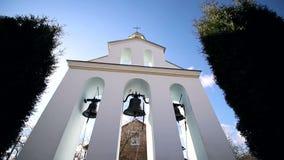 Campane di chiesa un giorno soleggiato in un forte vento Il vento scuote gli alberi vicino al campanile e Sonechka splende in stock footage