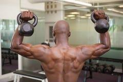 Campane di sollevamento del bollitore dell'uomo muscolare in palestra Fotografia Stock