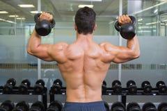 Campane di sollevamento del bollitore dell'uomo muscolare in palestra Fotografia Stock Libera da Diritti