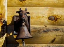 Campanello del metallo sotto forma di testa di una mucca con una campana intorno al suo collo immagine stock libera da diritti
