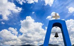 Campanile del ` s della chiesa in Grecia Incrocio sulla cima e sulla campana Nuvole sul fondo del cielo blu, copyspace Fotografia Stock