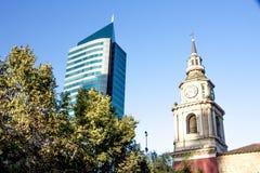 Campanile molto vecchio della chiesa con l'orologio, accanto ad una costruzione blu ultra moderna Fotografie Stock Libere da Diritti