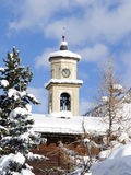 Campanile with snow and trees. A picture of a campanile full of snow from a mountain church in Livigno, Italy Stock Photo