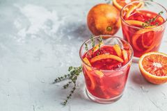 Campari or alcohol cocktail with Sliced Sicilian Blood oranges. And fresh red orange juice on light gray concrete background, copy spice, shallow depth of the stock photos