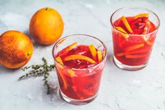 Campari or alcohol cocktail with Sliced Sicilian Blood oranges. And fresh red orange juice on light gray concrete background, copy spice, shallow depth of the stock image