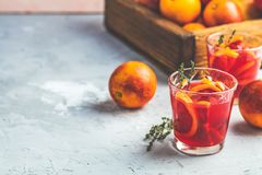 Campari or alcohol cocktail with Sliced Sicilian Blood oranges. And fresh red orange juice on light gray concrete background, copy spice, shallow depth of the stock photo