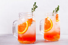 Campari and vermouth cocktail with oranges, garnished with thyme. Royalty Free Stock Photos