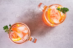 Campari and vermouth cocktail with oranges, garnished with thyme. Royalty Free Stock Image