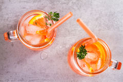 Campari and vermouth cocktail with oranges, garnished with thyme. Stock Photography