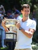 Campeón 2019 de Abierto de Australia Novak Djokovic de Serbia que presenta con el trofeo de Abierto de Australia en el jardín bot fotos de archivo
