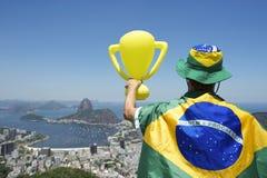 Campeón del Brasil que sostiene el trofeo envuelto en la bandera brasileña Río fotos de archivo