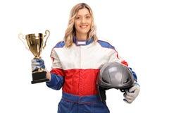 Campeón femenino de las carreras de coches que sostiene un trofeo imagen de archivo libre de regalías