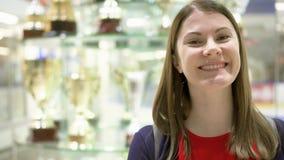 Campeón orgulloso de la mujer joven que se coloca cerca de soporte con los premios de los deportes Tazas de oro del ganador en ba metrajes