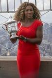 Campeón Serena Williams del US Open 2014 que presenta con el trofeo del US Open en el top de Empire State fotos de archivo