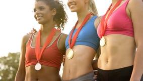 Campeões fêmeas da equipa nacional que levantam na frente das câmeras, orgulho da nação imagens de stock