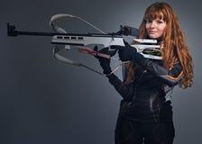 Campe?n femenino del Biathlon del pelirrojo que apunta con un arma competitivo imagen de archivo libre de regalías