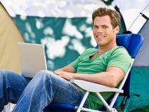 Campeggiatore che per mezzo del computer portatile Fotografia Stock Libera da Diritti