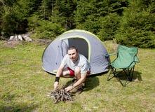 Campeggiatore che prova ad accendere un fuoco Fotografie Stock