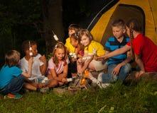 Campeggiatori che si siedono con la caramella gommosa e molle vicino al falò fotografie stock libere da diritti