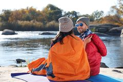 Campeggiatori che si siedono in sacchi a pelo sulla spiaggia immagini stock