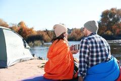 Campeggiatori che si siedono in sacchi a pelo sulla spiaggia selvaggia immagini stock