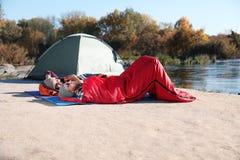 Campeggiatori che si trovano in sacchi a pelo sulla spiaggia immagini stock libere da diritti