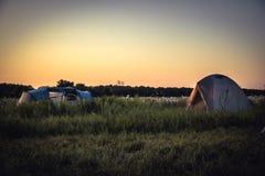 Campeggio con le tende di campeggio su fondo sul campo rurale di estate e sul cielo arancio di tramonto durante le vacanze in cam Immagine Stock