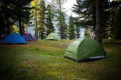 Campeggio e tenda di avventure sotto l'abetaia vicino ad acqua Fotografia Stock Libera da Diritti