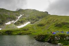 Campeggio selvaggio nel lago alpino durante la stagione estiva Immagine Stock
