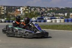 Campeonato de Karting El conductor en los karts que llevan el casco, compitiendo con el traje participa en raza del kart Demostra Fotografía de archivo libre de regalías