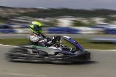 Campeonato de Karting El conductor en los karts que llevan el casco, compitiendo con el traje participa en raza del kart Demostra Imagen de archivo
