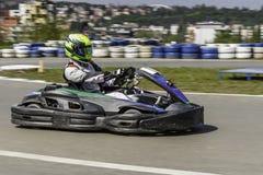 Campeonato de Karting El conductor en los karts que llevan el casco, compitiendo con el traje participa en raza del kart Demostra Foto de archivo