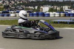 Campeonato de Karting El conductor en los karts que llevan el casco, compitiendo con el traje participa en raza del kart Demostra Foto de archivo libre de regalías