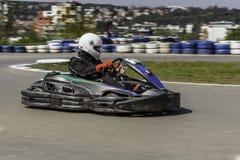 Campeonato de Karting El conductor en los karts que llevan el casco, compitiendo con el traje participa en raza del kart Demostra Fotos de archivo libres de regalías