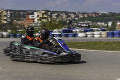 Campeonato de Karting O motorista nos karts que vestem o capacete, competindo o terno participa na raça do kart Mostra de Karting Fotografia de Stock Royalty Free