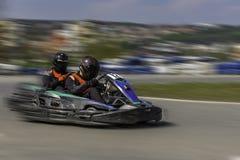Campeonato de Karting O motorista nos karts que vestem o capacete, competindo o terno participa na raça do kart Mostra de Karting Foto de Stock Royalty Free