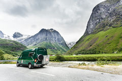 Camper car in norwegian mountains. Tourism vacation and travel. Camper van and norwegian mountains landscape Royalty Free Stock Image