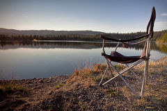 Camper Chair. A foldable chair set up by a still mountain lake on a beautiful summer day Stock Photo