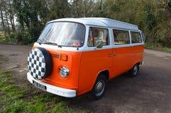 Camper classico di Volkswagen in bianco ed in arancio fotografia stock