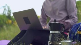 Camper dans les montagnes Une fille prépare le café sur une machine de café de geyser Une femme travaille à distance pour un ordi
