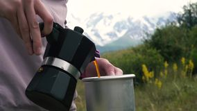 Camper dans les montagnes Une fille prépare le café sur une machine de café de geyser Une femme verse dans une tasse en aluminium clips vidéos