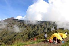 Camper dans les nuages sur le cratère de mt Rinjani Photos stock